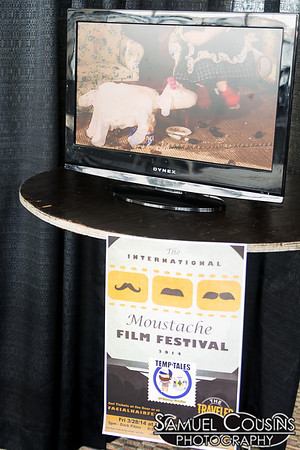 Films from the International Moustache Film Festival playing on a small screen at the Facial Hair Farmer's Market