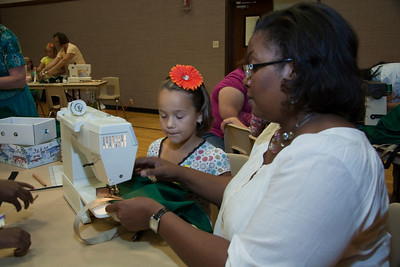 Mylah Mills Osifo helps girl sew