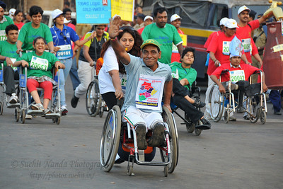 People with disabilities taking part in the race with wheelchairs and walking sticks. Standard Chartered Mumbai Marathon 2010. Mumbai, India. January 17, 2010.