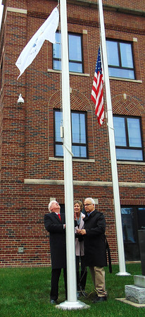 Debbie Blank | The Herald-Tribune Mayor Mike Bettice (from left) raises a new Indiana Bicentennial flag in front of the Memorial Building Dec. 11, the date the state was founded 200 years ago, with the help of Carolyn Dieckmann and Bill Flannery. It was at half mast due to the death of astronaut and Sen. John Glenn Dec. 8.