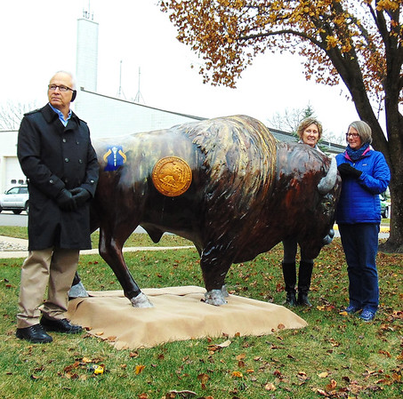 Debbie Blank | The Herald-Tribune<br /> Batesville High School art teacher Mary K Cambron (from right) painted the city's 5-foot-tall fiberglass bison sculpture in her garage with the help of fellow teacher Kyle Hunteman (not present). With her are Batesville Bicentennial Committee chairmen Carolyn Dieckmann and Bill Flannery.