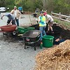 Huge piles of compost and wood chips get apportioned into waiting wheel barrels.