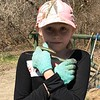 This volunteer is happy to show off the garter snake she found basking in a patch of sunlight.