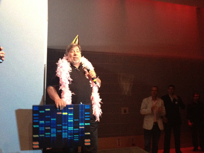 Woz speaks to the crowd alongside his present, art based on his DNA.