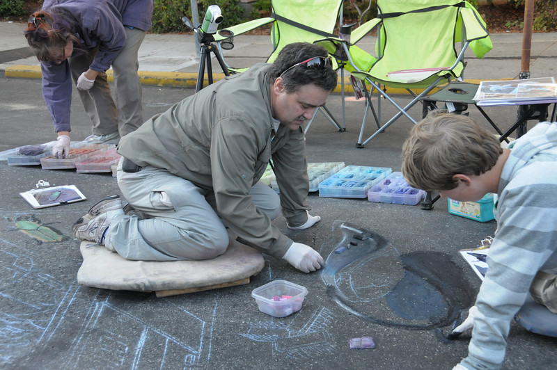 Wayne Renshaw and Alex work on the mouse, while Cheryl cleans up the chalk