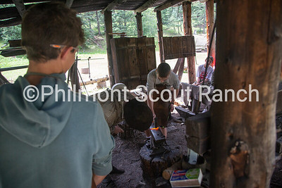 Charles Fournier holds a piece of hot metal as a scout hammers it at Black Mountain camp on Sunday, August 11, 2019 at Philmont Scout Ranch in Cimarron, New Mexico.