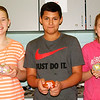 "Debbie Blank | The Herald-Tribune<br /> Three students were among many who opted to paint rocks. Seventh-grader Sarah Weisenbach (from left) added a butterfly, sixth-grader Tug Jansen wrote ""SDMS Giving Back"" and seventh-grader Kylee Weber painted a heart and paw print. The creations were added to the school's Kindness Rocks Project. A box of stones in the lobby has a sign that suggests, ""Take one for inspiration. Share one for motivation. Leave one to help our garden grow!"""