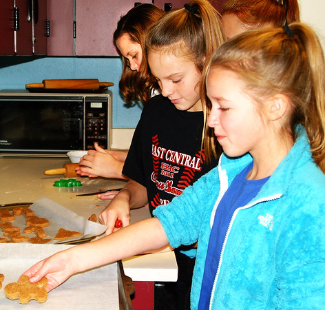 Debbie Blank | The Herald-Tribune<br /> Sixth-graders (from left) Myranda Bedford, Payge Callahan and Paiton Anthony make super simple peanut dog treats from a recipe provided by Family, Career and Community Leaders of America adviser Brenda Osman.