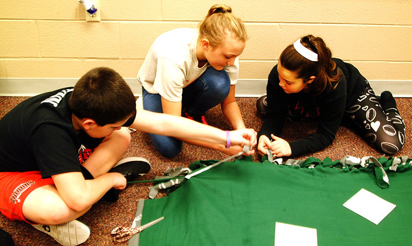 "Debbie Blank | The Herald-Tribune<br /> Sixth-grader Evan Wynn (from left) and seventh-graders Sam Mittermeier and Josey Mergenthal knot the border of a fleece blanket. Mergenthal said she was in a happy mood, calling the day ""very helpful and great!"""