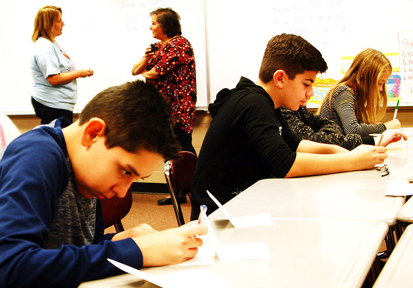 Debbie Blank | The Herald-Tribune<br /> Seventh-grader Cole Benegas (from left) and eighth-grader Alex Alderucci decide what to write to active military members to brighten their holidays.