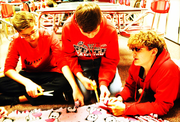 "Debbie Blank | The Herald-Tribune<br /> Eighth-graders (from left) Nick Hoffmeier, Jason Humble and Ian Johnston cut the edges of fleece material to make a blanket. Maycey Lewis said the blanket was destined for ""someone who needs it."""