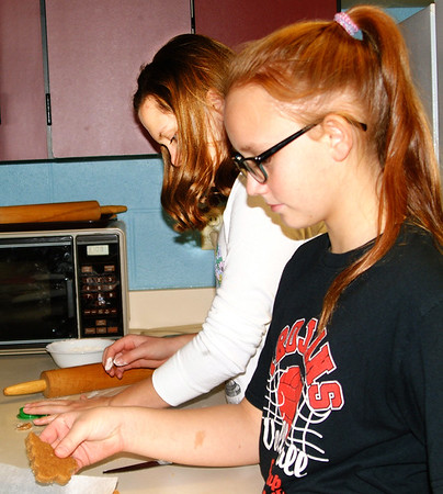 "Debbie Blank | The Herald-Tribune<br /> Sixth-grader Rachel Parnell's favorite part of making dog treats was shaping them with cookie cutters. With her is sixth-grader Myranda Bedford (left). They were supervised by family and consumer sciences teacher Tammi Corbin, who reported the day ""has gone pretty good."""