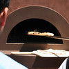 Hot pizza coming out of the outdoor wood fired pizza oven.