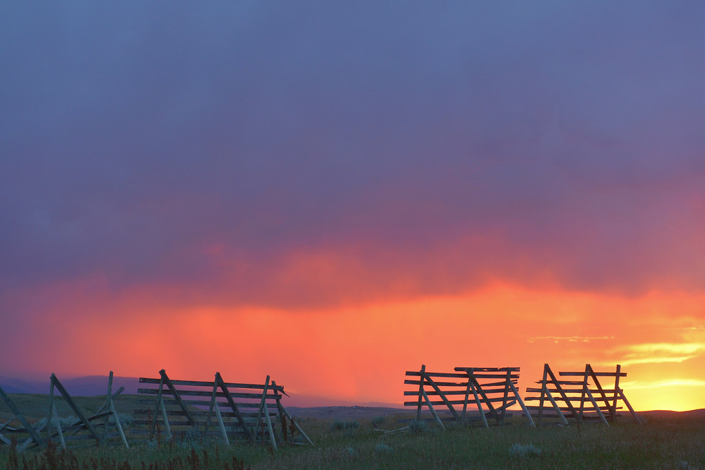 Justin Sheely | The Sheridan Press <br /> Thursday's sunset shines through a set of weathered snow fence on Soldier Creek Road. Smoke from nearby fires lends to spectacular color during sunrise and sunset.