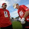 NFL Alumni Doug Flutie signs a game ball for a fan