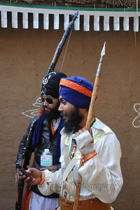 Sikh artists from Patiala in Nihang's martial art dress with weapons which includes cellphones.   Surajkund Crafts Mela 2011 held near Delhi in Faridabad, Haryana, North India. The annual Suraj Kund Mela (fair) is an event held in February each year where artisans, craftsmen, musicians & dancers come together and entral thousands of visitors. It is also a great shopping bonanza and delight to the palate with the range of food.
