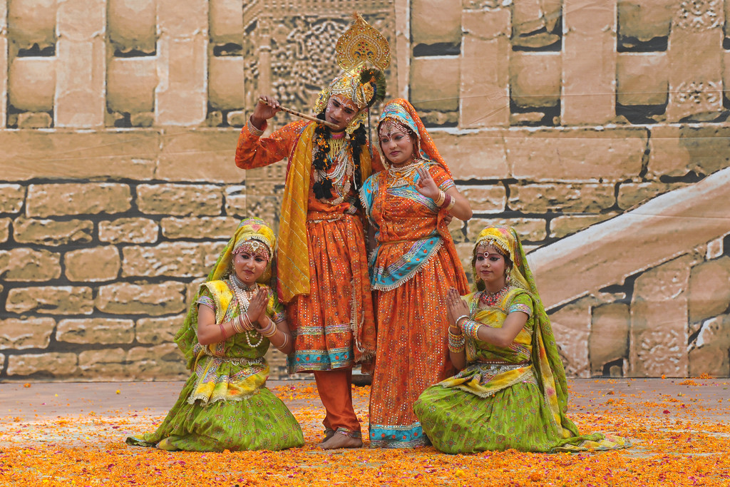Dancers from Mathura perform the Birj Ki Holi (Raas Leela) of Bhagwan Krishna and Radha at the open theatre called Chaupal at Suraj Kund Mela 2009. Generous sprinkle of the auspicious marigold petals as part of the performance. Held in Haryana (outskirts of Delhi), North India the Suraj Kund Mela is an annual fair held near Delhi. Folk dances, handicrafts and a lot of fun.