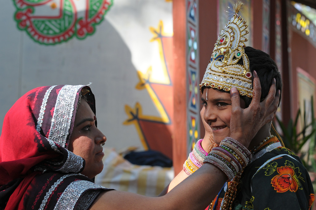A lady prepares a child artists at Surajkund Mela 2009, Haryana, North India. The theme state was MP (Madhya Pradesh). The Surajkund Crafts Mela is an annual fair held near Delhi. Folk dances, musical performances, handicrafts on display & sale and and a lot of fun & excitement for everyone.