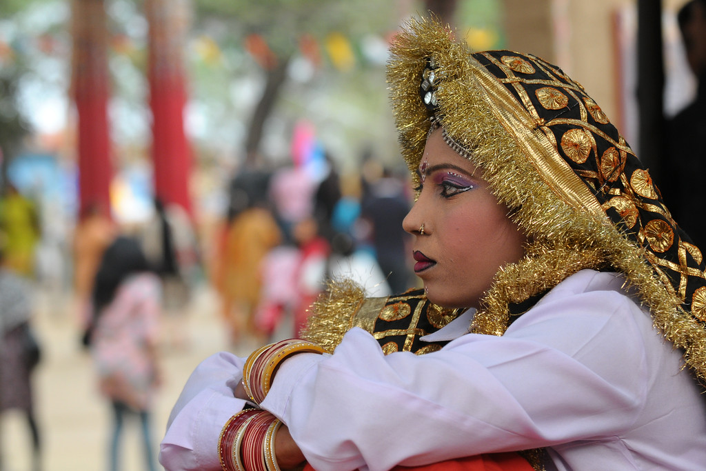 Young girl who is a dancer with the Haryanvi Group sitting and resting near the open theatre called Chaupal at Suraj Kund Mela 2009. Held in Haryana (outskirts of Delhi), North India, the Suraj Kund Mela is an annual fair held near Delhi. Folk dances, handicrafts and a lot of fun.