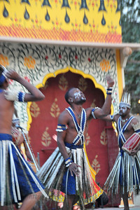 Siddi tribe dancer at Surajkund breaking a coconut with his head. The foot tapping and soul stirring music of their 'Siddhi Gorma' dance truly reflected the diverse culture of Gujarat. This dance traces its origins to the Afro music brought by african immigrants. Imran Siddi commenting on his tribal culture said that their tribes have got  an inclination towards religion & spiritualism and dance and music are the only forms of expression. He feels that it is a kind of a spiritual devotion to his ancestors every time he dances on the stage.  Siddi tribe performers at the open theatre called Chaupal at the Suraj Kund Crafts Mela 2010 which is an annual fair held near Delhi in February. Visitors get to experience folk dances, handicrafts and taste lots of delicious food.