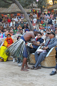 Displaying the two coconuts which he will soon crack with his bare head. Siddi tribe at Surajkund. The foot tapping and soul stirring music of their 'Siddhi Gorma' dance truly reflected the diverse culture of Gujarat. This dance traces its origins to the Afro music brought by african immigrants. Imran Siddi commenting on his tribal culture said that their tribes have got  an inclination towards religion & spiritualism and dance and music are the only forms of expression. He feels that it is a kind of a spiritual devotion to his ancestors every time he dances on the stage.  Siddi tribe performers at the open theatre called Chaupal at the Suraj Kund Crafts Mela 2010 which is an annual fair held near Delhi in February. Visitors get to experience folk dances, handicrafts and taste lots of delicious food.