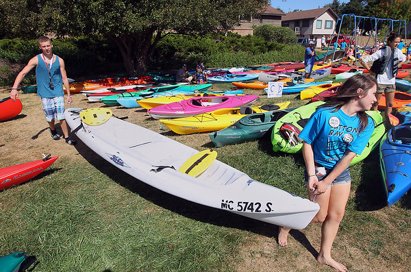 Record-Eagle/Keith King<br /> Angela Hernandez, right, 17, and Casey Cross, 16, both of Suttons Bay, carry a kayak prior to setting it down in the appropriate row Saturday, September 1, 2012 for the Suttons Bay Floatilla which hopes to break the record of a raft of 1,902 canoes and kayaks as recognized by the Guiness Book of World Records. Proceeds from the event go to the Suttons Bay Schools Student Activities Fund.