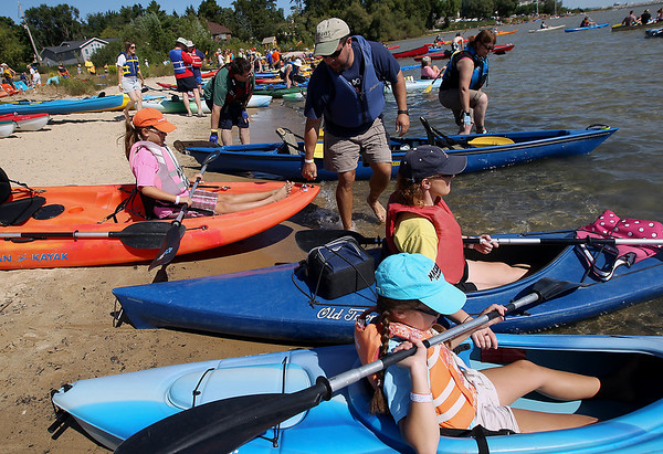 Record-Eagle/Keith King<br /> Scott Doederlein, of Gaylord, pulls his daughter, Ally Doederlein, 9, closer to water as his daughter Emma Doederlein, from bottom, 12, and wife, Ann Doederlein, wait to paddle out in kayaks Saturday, September 1, 2012 for the Suttons Bay Floatilla which hopes to break the record of a raft of 1,902 canoes and kayaks as recognized by the Guiness Book of World Records. Proceeds from the event go to the Suttons Bay Schools Student Activities Fund.