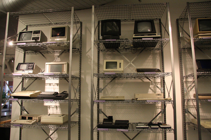 More artifacts, including a Macintosh TV (top, black one), and an Atari (right column, third shelf from the top, on the right)