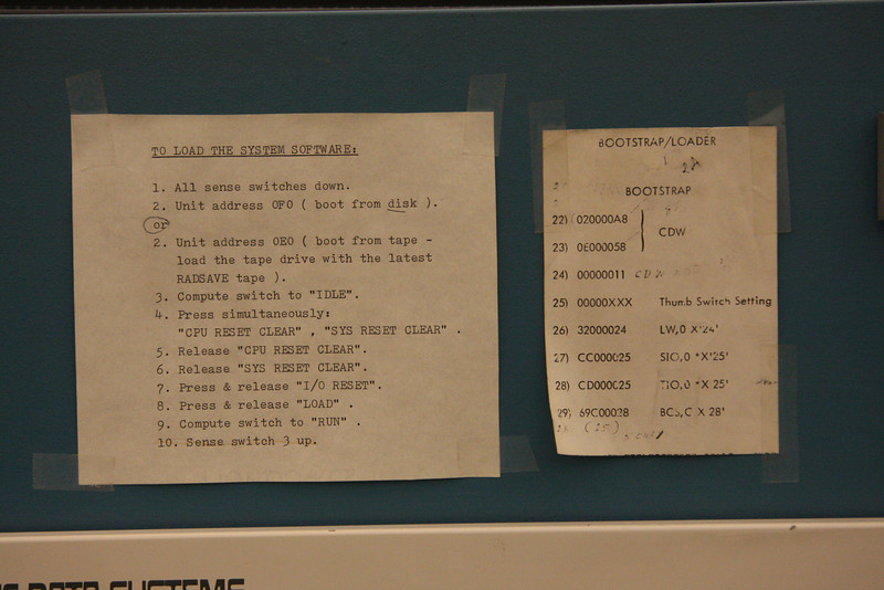 """The instructions for loading software on the XDS Sigma 5 include <br /> pressing and releasing a series of cryptically labeled buttons in particular orders. The person who ran this machine also taped up a cheat-sheet of bootstrap codes. Perhaps the manufacturer thought, 'If we make it obscure enough, only a few people can run it, thus confirming the system's multi-million dollar worth."""""""