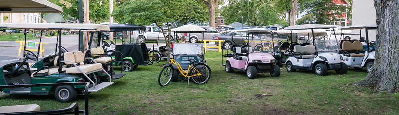 Concert-goers' golf carts and bicycles parked outside the auditorium