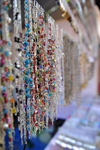 Assorted trinklets and necklaces. At Taj Mahotsav about 400 legendary artisans from different parts of the country get an opportunity to display their exquisite works of art. To name a few among them  are the wood/stone carvings from Tamil Nadu, Bamboo/cane work from North East India, Paper mash work from South India and Kashmir, the marble and zardozi work from Agra, wood carving from Saharanpur, brass wares from Moradabad, hand made carpets from Bhadohi, Pottery from Khurja, Chikan work from Lucknow, silk & zari work from Banaras, shawls & carpets from Kashmir/Gujarat and hand printing from Farrukhabad and Kantha stitch from west Bengal etc.  Taj Mahotsav (Hindi: ताज महोत्सव, Urdu: تاج مہوتسو, translation: Taj Jubilee) is an annual 10 day festival that takes place from 18th to 27th  February. The event is held at Shilpgram in Agra, India. This carnival is a vibrant platform that brings together India's finest craft and culture at one single place. It is a festive introduction to  India as a whole and Uttar Pradesh in particular, where the extensive range of  art,  craft, culture and cuisine are on display. Every year in February, tourists flock to Agra for this mega event, just a stone throw from the majestic Taj Mahal. This festival invokes the memories of old Mughal era and nawabi style prevalent in Uttar Pradesh in 18th and 19th centuries.  Taj Mahotsav Ek Utsav Pyar Ka, Celebrating Immortal Love, 18-27 February, 2010. A festival of art, craft, culture and cusuine. North, Uttar Pradesh (UP), North India.