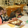 The girls are helping to prepare pins for a bug collection at the museum.