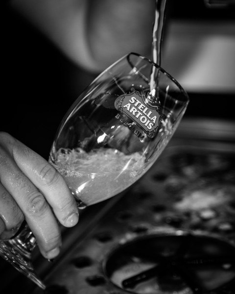 I chose to do these photos in black and white so you can focus more on the glass and process rather than the color of beer.<br /> The glass is tipped on the side in order to prevent from too head forming at once.
