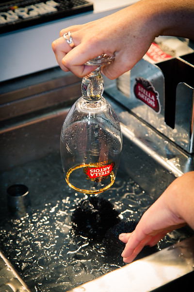 The glass is pulled from a rack, visually inspected, and dipped into cold water with a scrub.  The ice bath cools the glass to the same temperature of the beer and the scrub cleans out any impurities.  A hot glass affects the flavor and quality of the beer.<br /> <br /> Cleanliness is next to godliness they say.