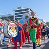 Superhero Band marching along city street past buildings