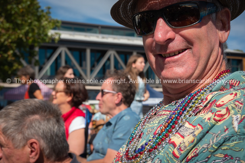Enjoying the event, mature man with beads and colorful shirt smiles at National Jazz Festival
