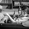 Two young women sitting back of convertible vintage car close-up and in street.