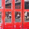 Vintage red multi-paned doors with reflections of street scene and people in panes.