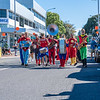 Superhero Band marching along city street past buildings and people