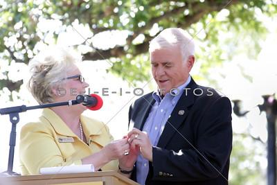 Jean Johnson Main Street Manager giving Congressman John Carter a pin.