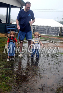 8/27/2011 Mike Orazzi | Staff Michael Kather and his twins Lilly and Henry, 2 1/2, splash through puddles while at the Terryville Country Fair on Saturday morning.
