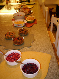 From front to back:  Cooked cranberry sauce, Raw cranberry/orange relish, Three stuffings, Mashed Rutabagas, Creamed onions, Sweet potatos and apples, Turducken...