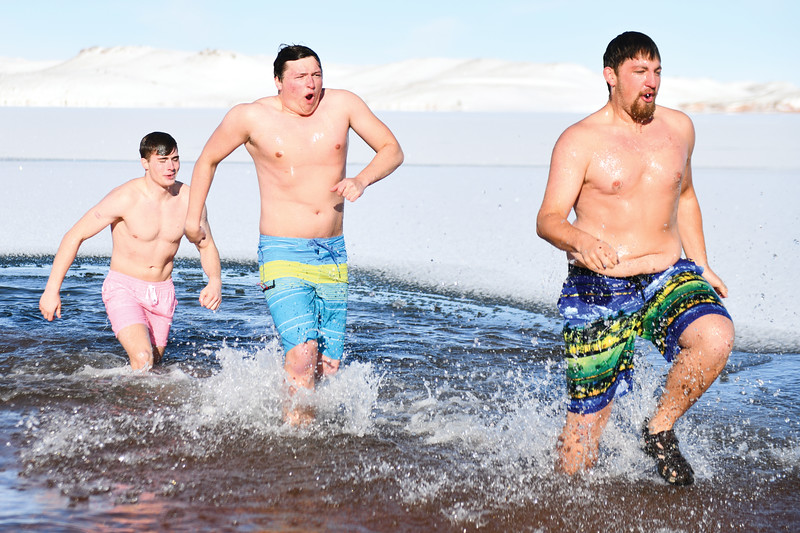 Matthew Gaston | The Sheridan Press<br>From left, Carter Mangus, Connor Jorgenson and Davis Alder run out of Lake DeSmet after the Polar Bear Plunge Tuesday, Jan. 1, 2019.