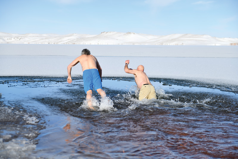 Matthew Gaston | The Sheridan Press<br>From left, Scott and Rob Forister dive into Lake DeSmet during the Polar Bear Plunge Tuesday, Jan. 1, 2019.