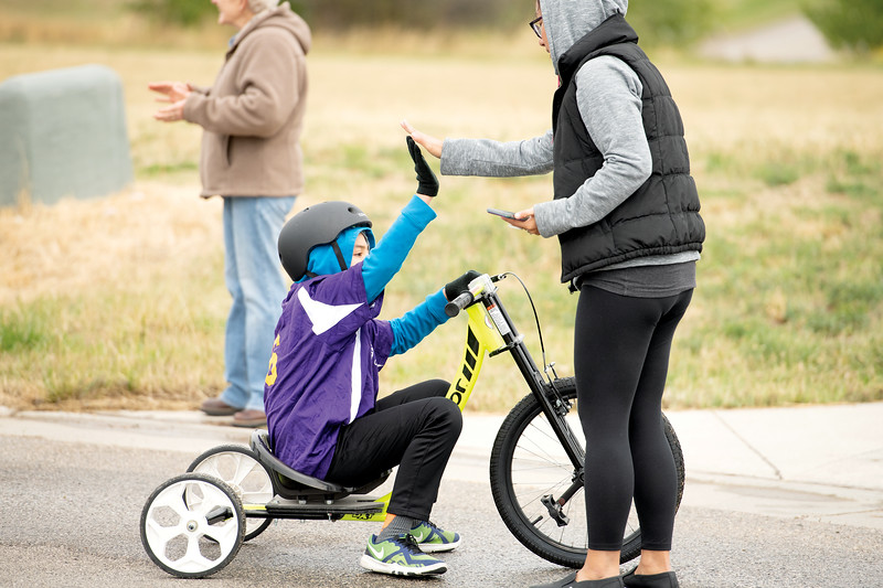 Matthew Gaston | The Sheridan Press<br>Maxwell Jimmerson high fives his mom Jennifer Jimmerson after completing the 500-meter cycling race for the 2019 Special Olympics Area IV Fall Games Friday, Sept. 27, 2019.