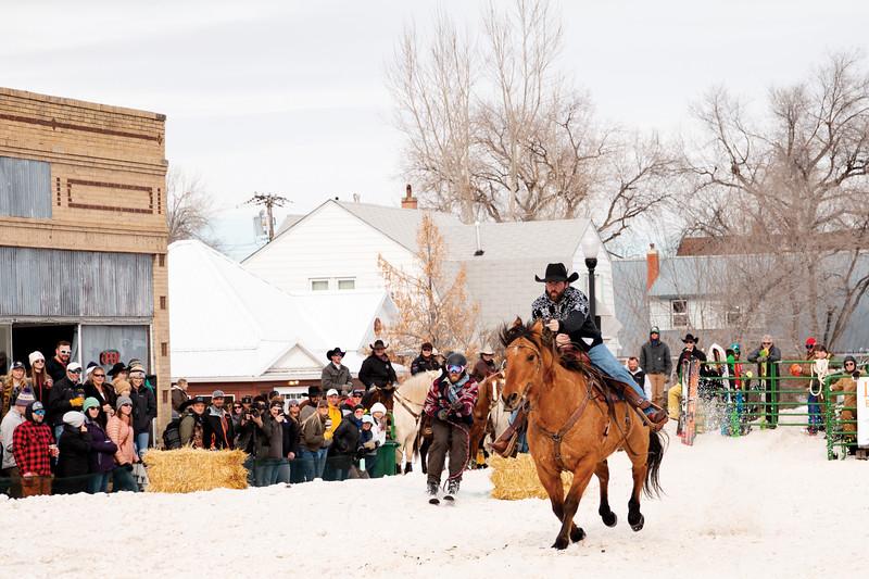 Matthew Gaston | The Sheridan Press<br>Rider Nick McDonald and skier Jeff Stull race out of the starting gate at the Sheridan WYO Winter Rodeo Saturday, Feb. 23, 2019.