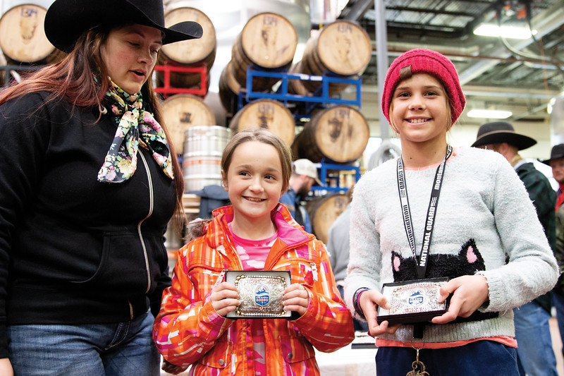 Matthew Gaston | The Sheridan Press<br>Bailey McLean, left, presents rider Kimber Cook, 9, and skier Phoebe Alverson, 11, with the awards for first place in the youth class at the Sheridan WYO Winter Rodeo Saturday, Feb. 23, 2019.