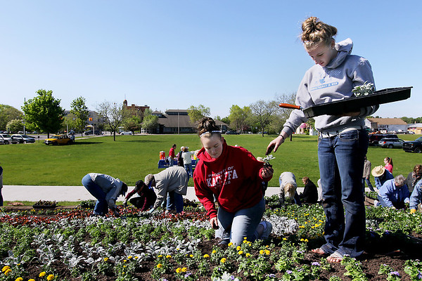 Record-Eagle/Keith King<br /> Morgan Robinson, right, and Ashley Plut, both Traverse Bay Area Intermediate School District Agriscience students, along with members of The Friendly Garden Club and others, plant flowers in the logo garden Thursday, June 2, 2011 at the Open Space.