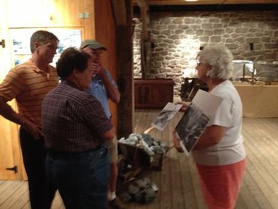 Guests view historical photographs in the Charcoal Barn at the annual MABA picnic at Joanna Furnace, Aug. 20, 2013.