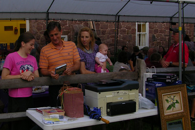 State Rep. Mark Gillen and his family look over some of the auction items at the annual MABA picnic at Joanna Furnace, Aug. 20, 2013.